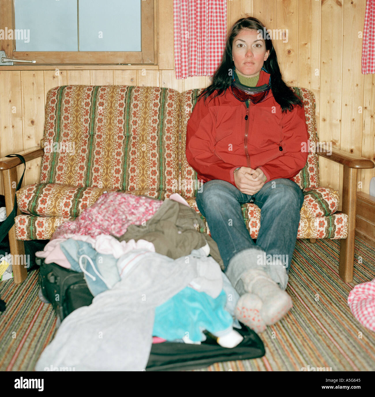 female sitting on a couch in a chalet in the alps - Stock Image