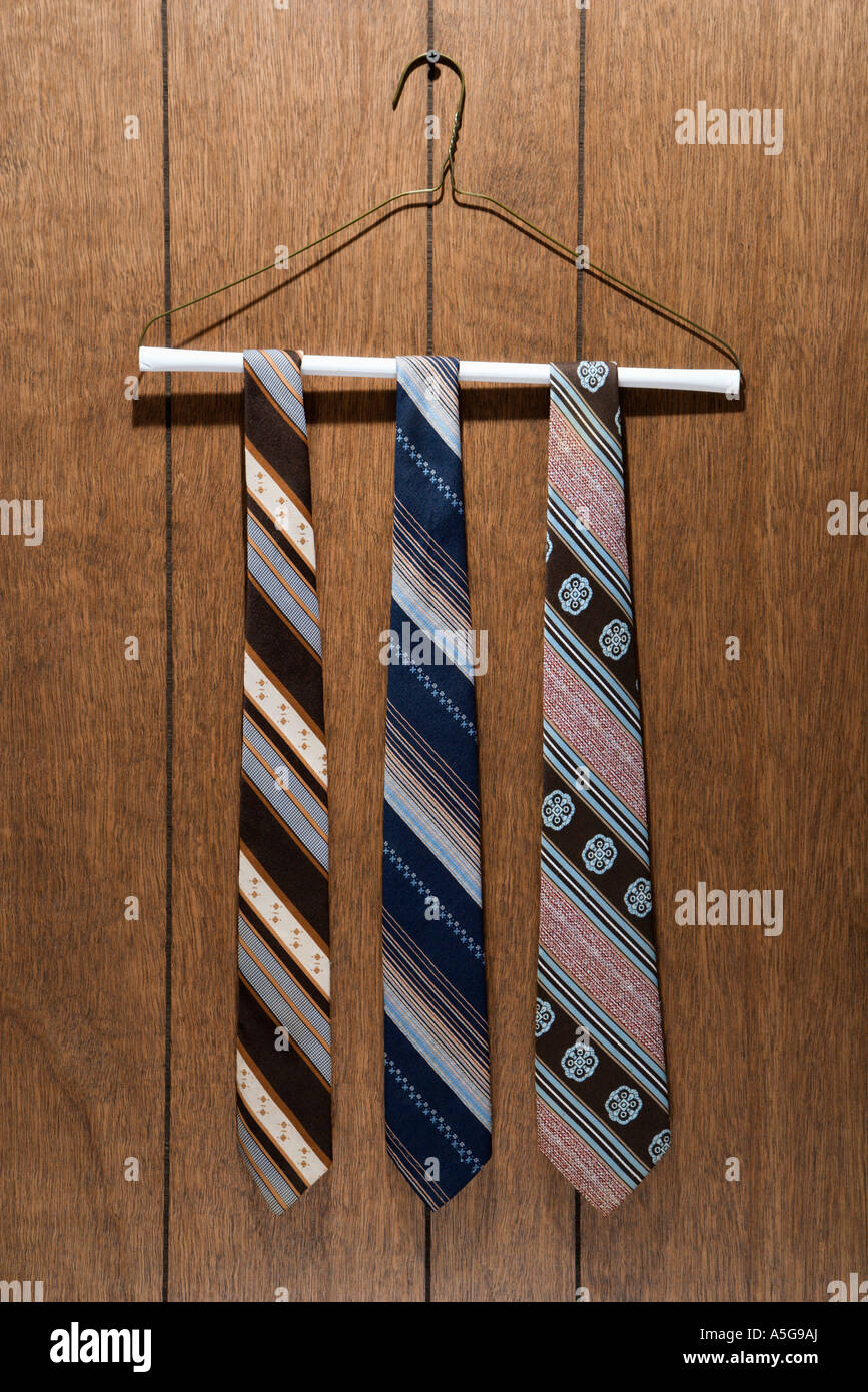 Three retro ties hanging on a wire hanger against wood paneling - Stock Image