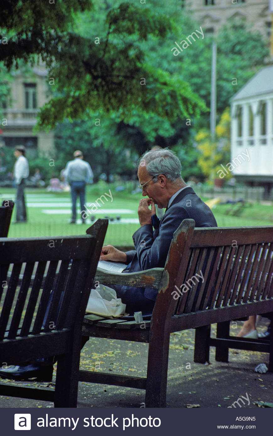 A businessman eats his sandwich at lunch, reading while sitting in the park at Finsbury Circus, watching bowls; London - Stock Image