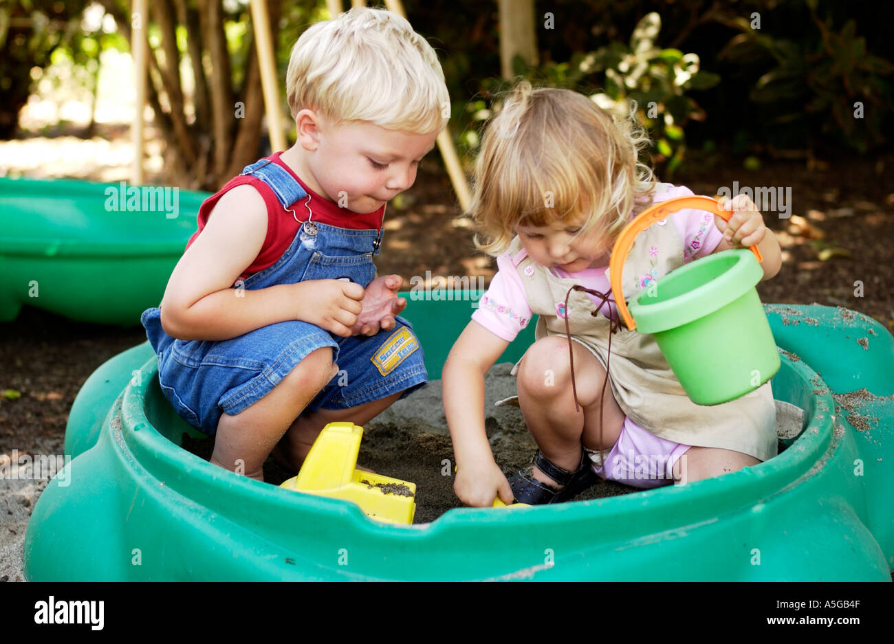 Two year old boy and girl playing together in sandbox - Stock Image