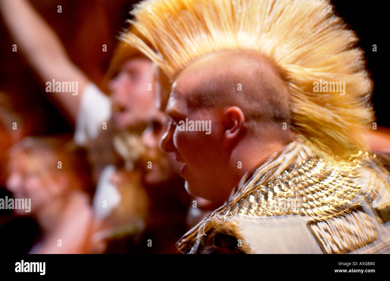 Teenager with Mohawk at punk rock show - Stock Image