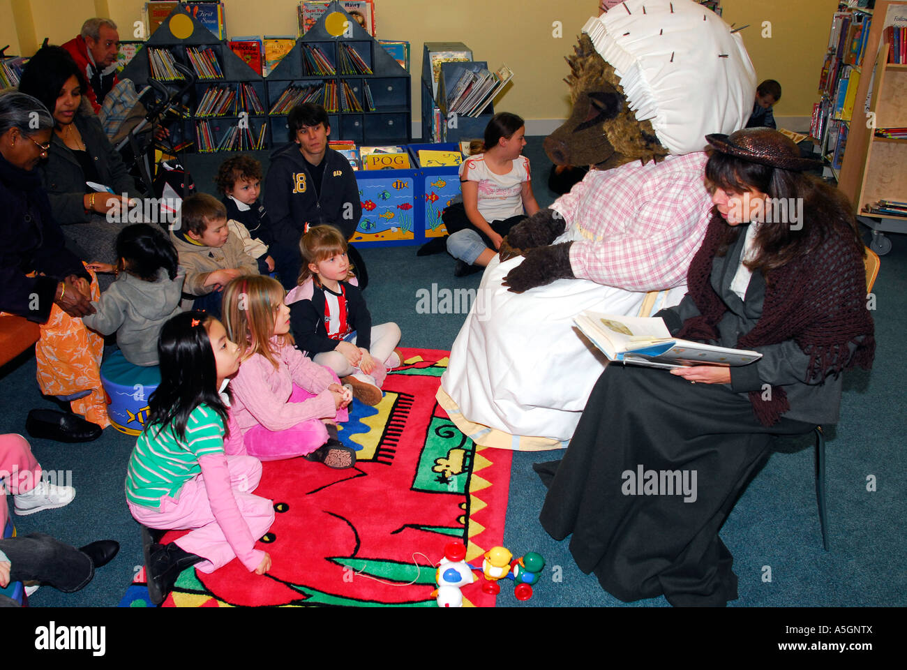 Parents with their children during half term listening to a book reading session of Beatrix Potter books, Feltham, - Stock Image