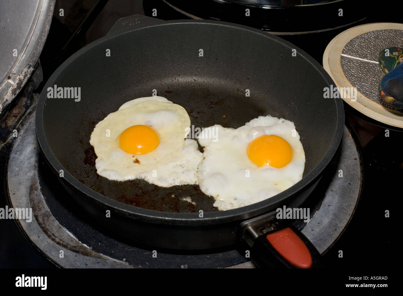 Two eggs frying in large black teflon pan Cotswolds UK - Stock Image