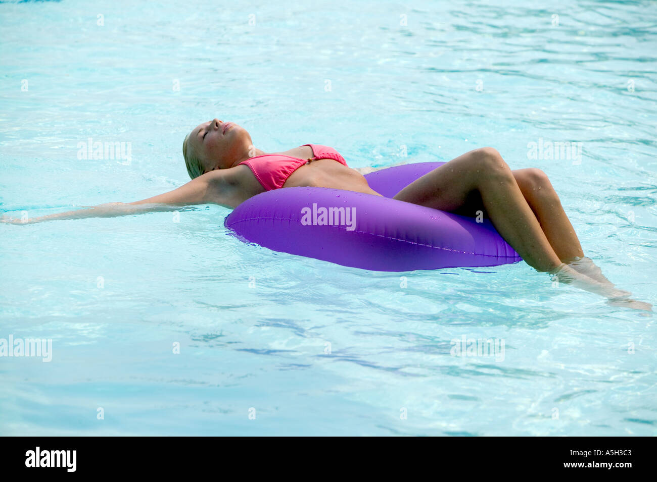 A young woman floating in a pool - Stock Image