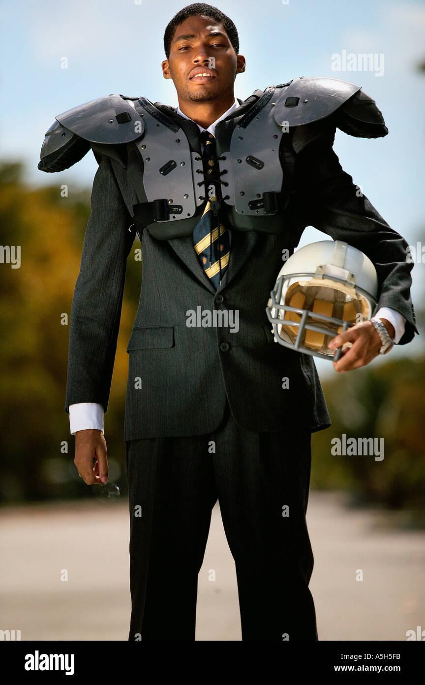 Businessman wearing american football uniform - Stock Image