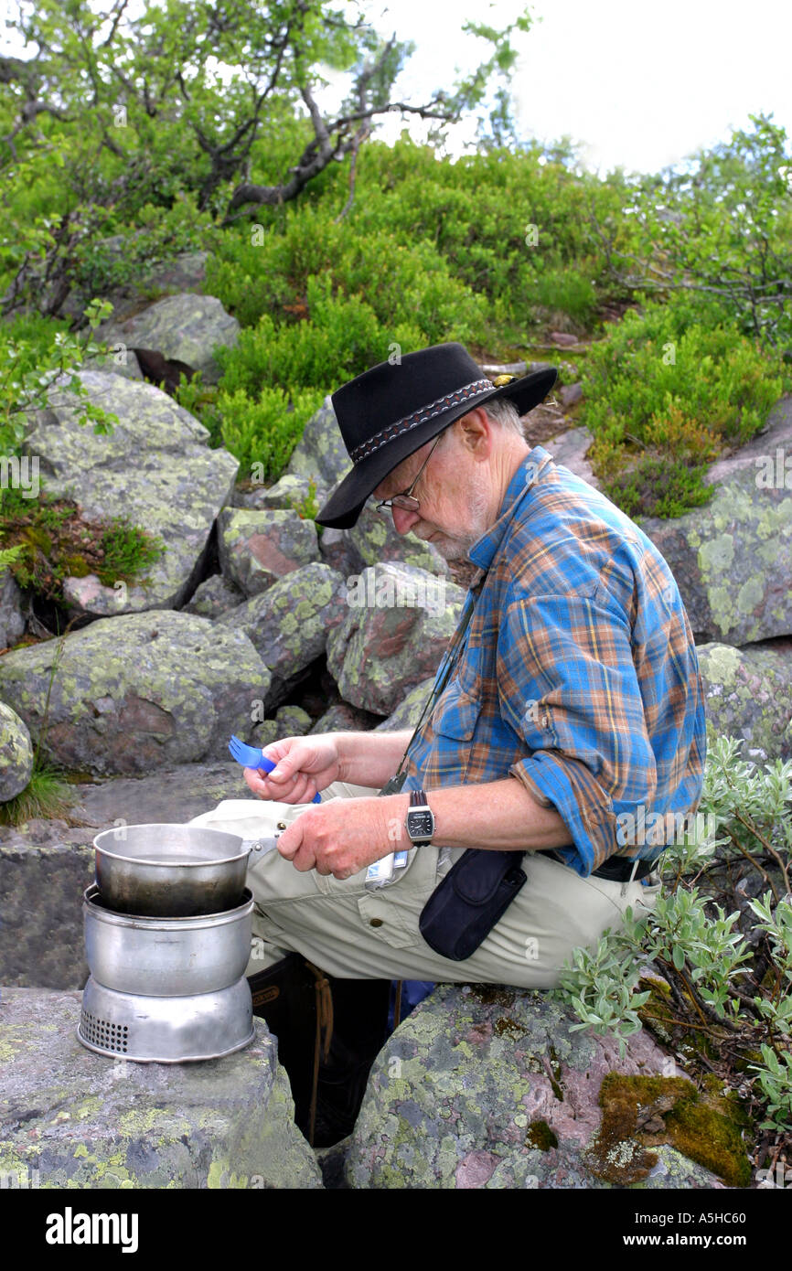 Man cooking food outside in the swedish mountains - Stock Image