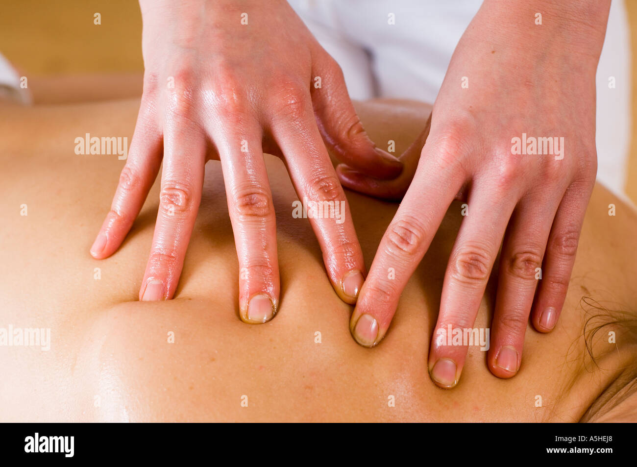hands giving a massage to a back - Stock Image