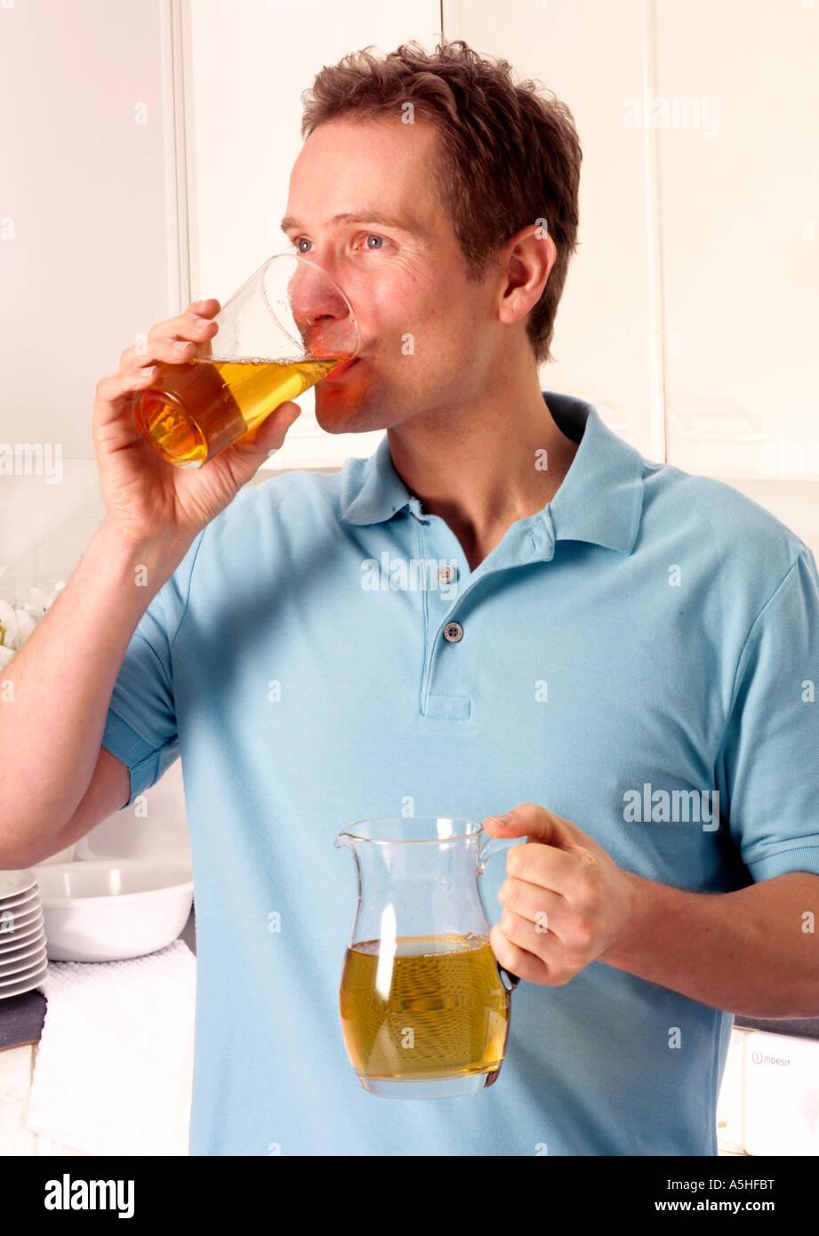 MAN IN KITCHEN DRINKING APPLE JUICE Stock Photo: 11316731 - Alamy