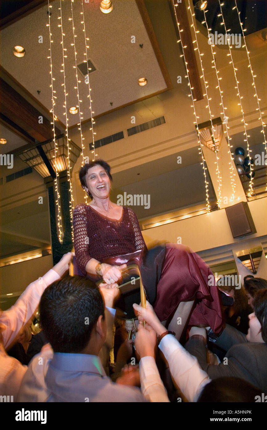Detroit Michigan Julie Hurwitz is lifted on a chair at a party following the bar mitzvah of her son - Stock Image