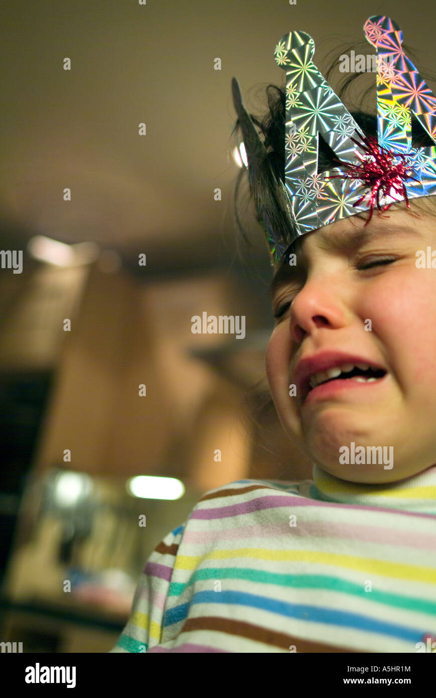 little girl wearing festive crown crying - Stock Image
