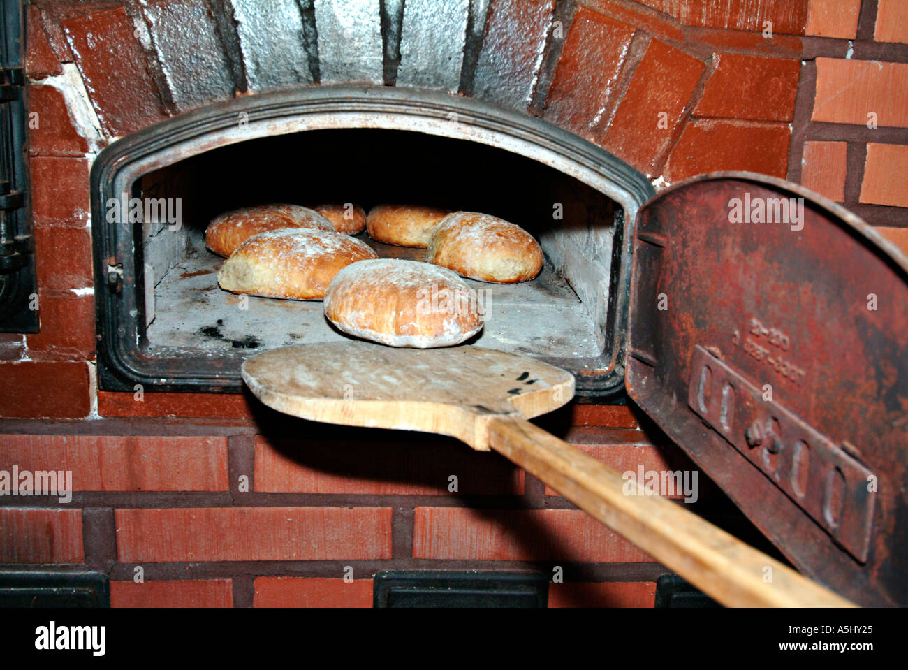 PR outloading loaves of bread out of an made old stove of stone - Stock Image