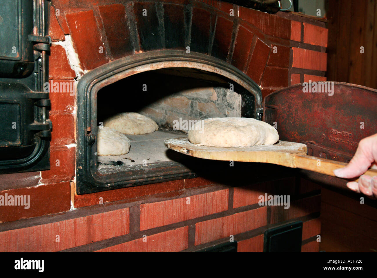 PR getting loaves of bread in an old stove made of stone - Stock Image
