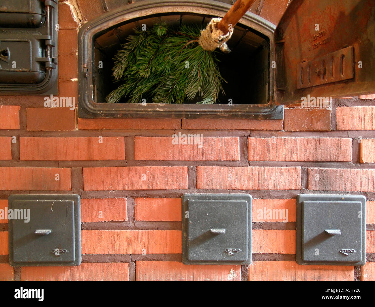 PR Cleaning A Baking Oven Of An Old Wood Heated Kitchen Stove With Braches Pines