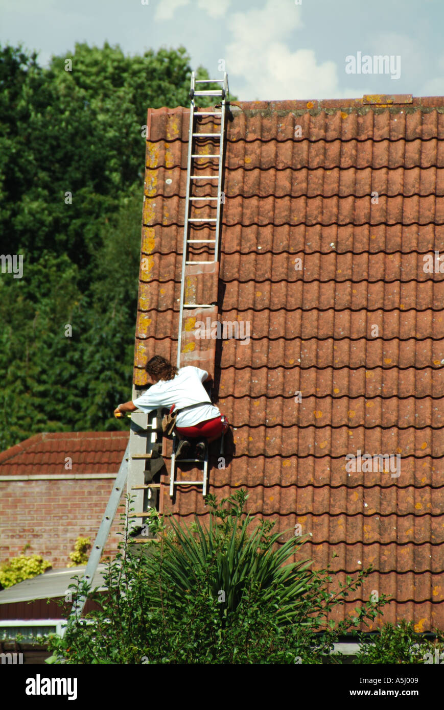 Roof tile repairs in progress at verge to detached house - Stock Image
