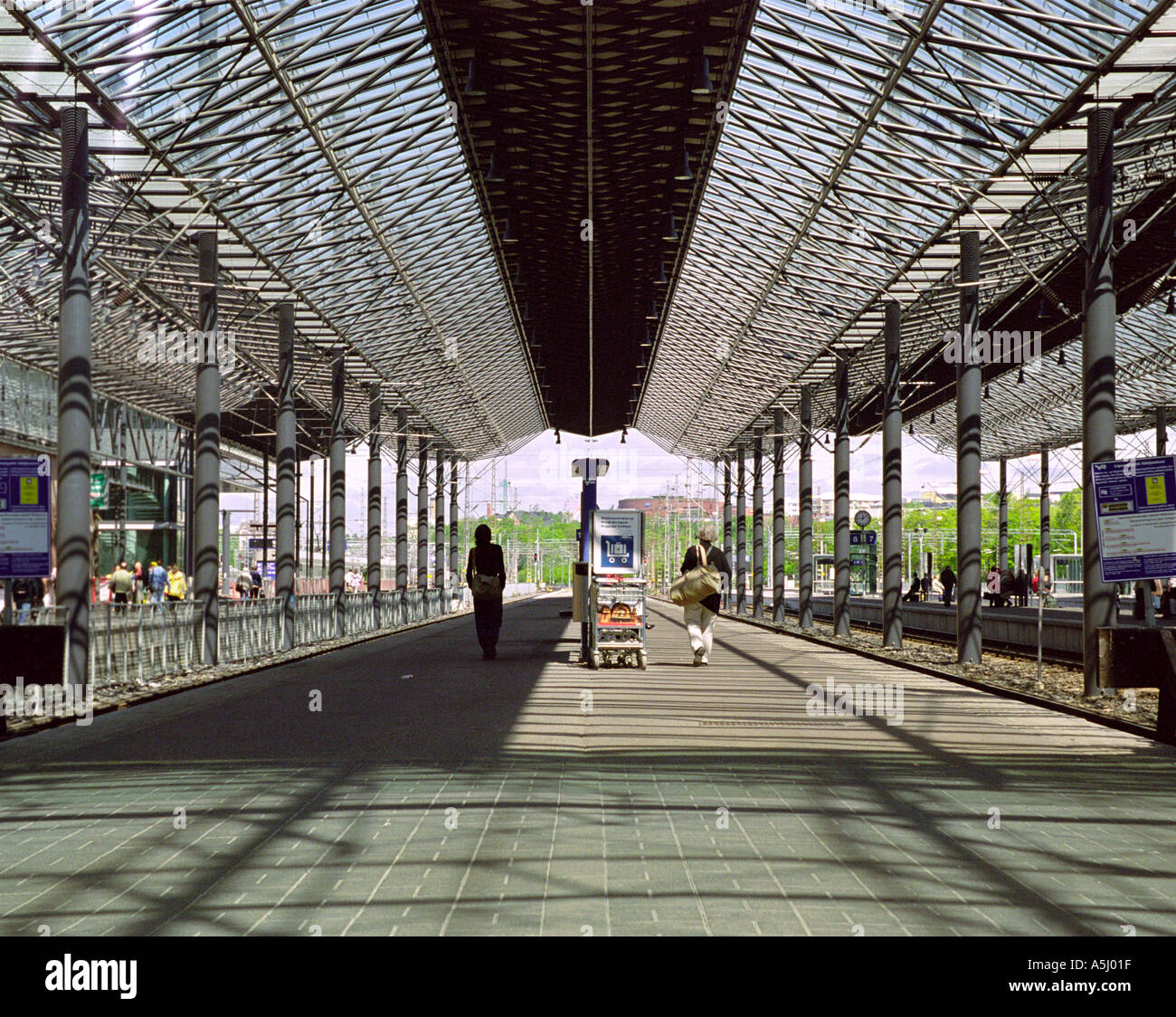 Two people walking down the platform at Helsinki railway station Finland - Stock Image