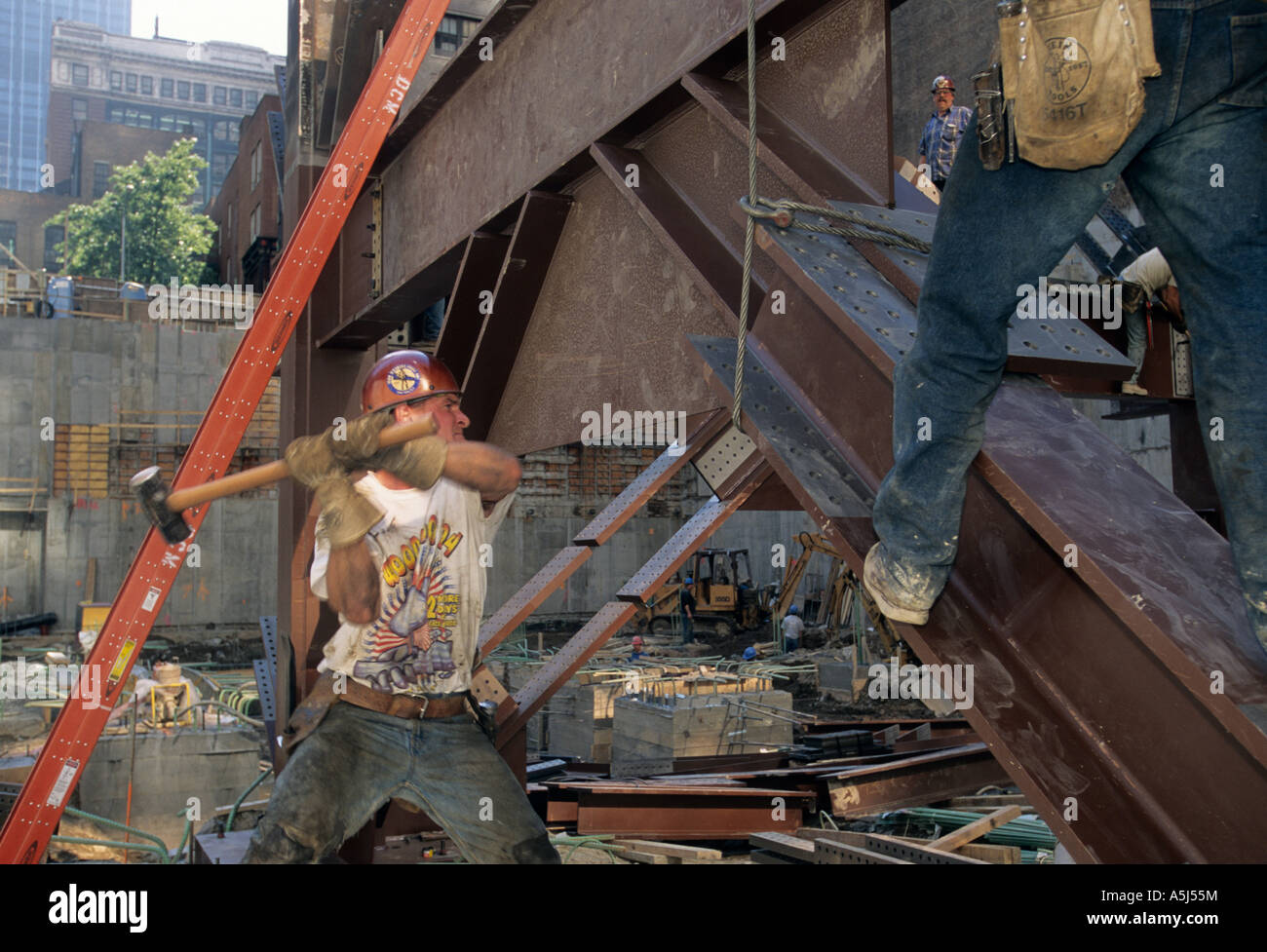 Iron worker use sledge hammer to line up bolt holes on 24,000 pound