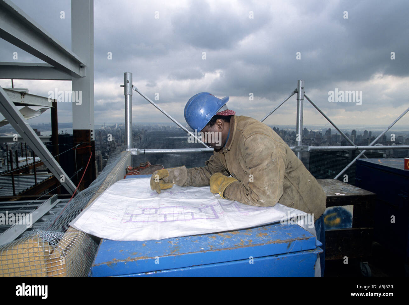 Welder looks over blueprints at the top of the new Random House building at 1745 Broadway in New York City - Stock Image
