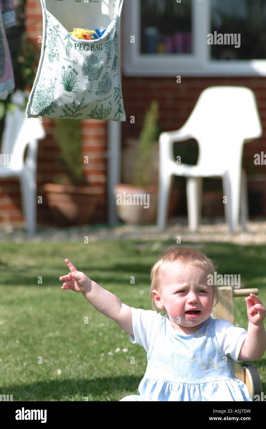 British toddler in garden crying London UK - Stock Image