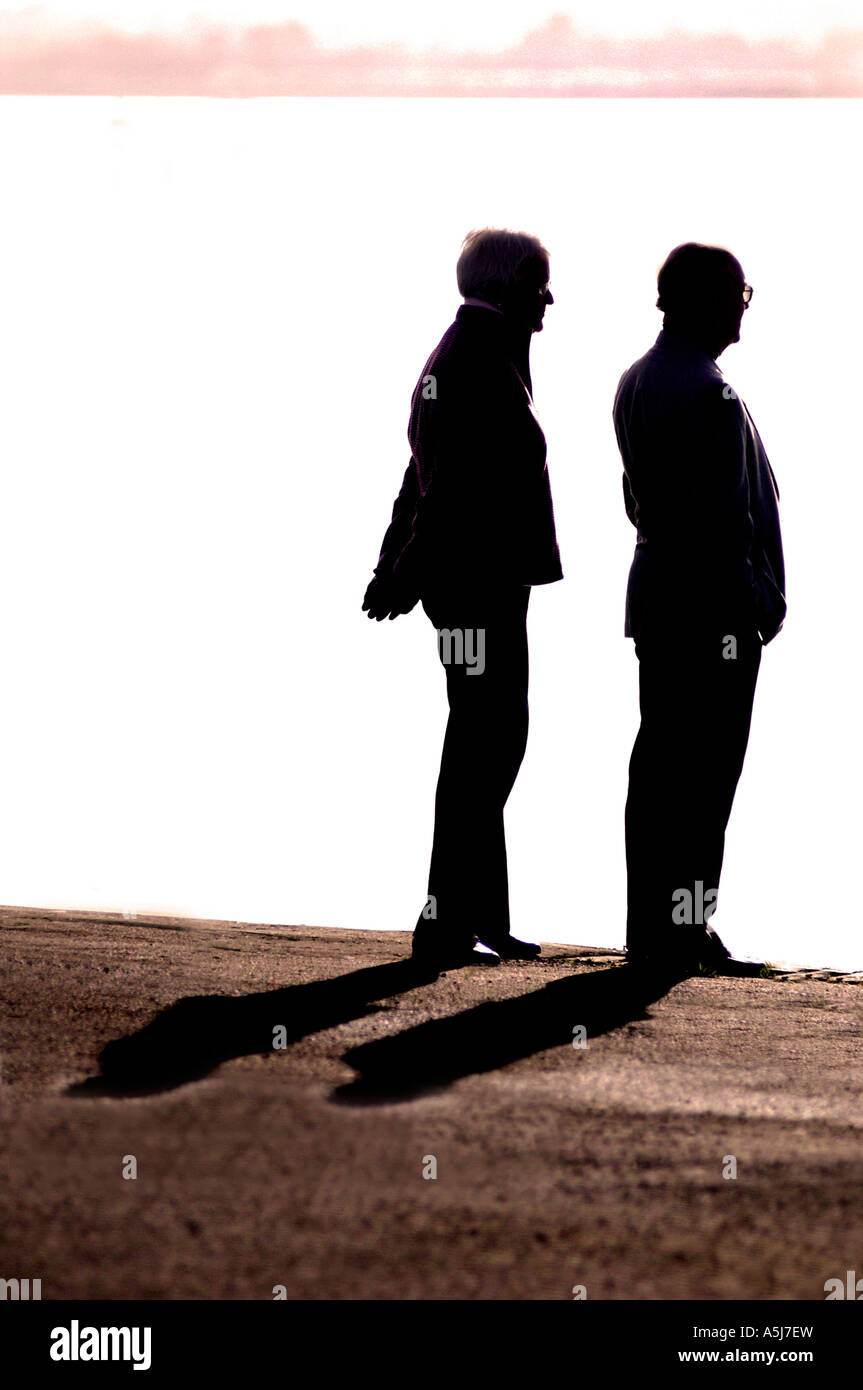 British couple pensioner retired together at sunset UK silhouette - Stock Image