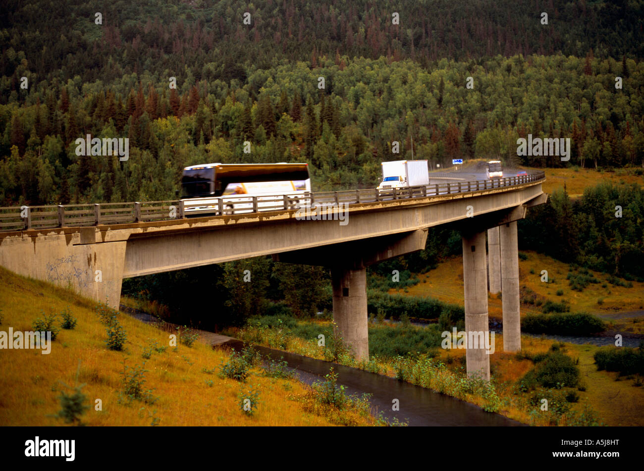 Tourist bus crossing a bridge on the Seward Highway in Alaska - Stock Image