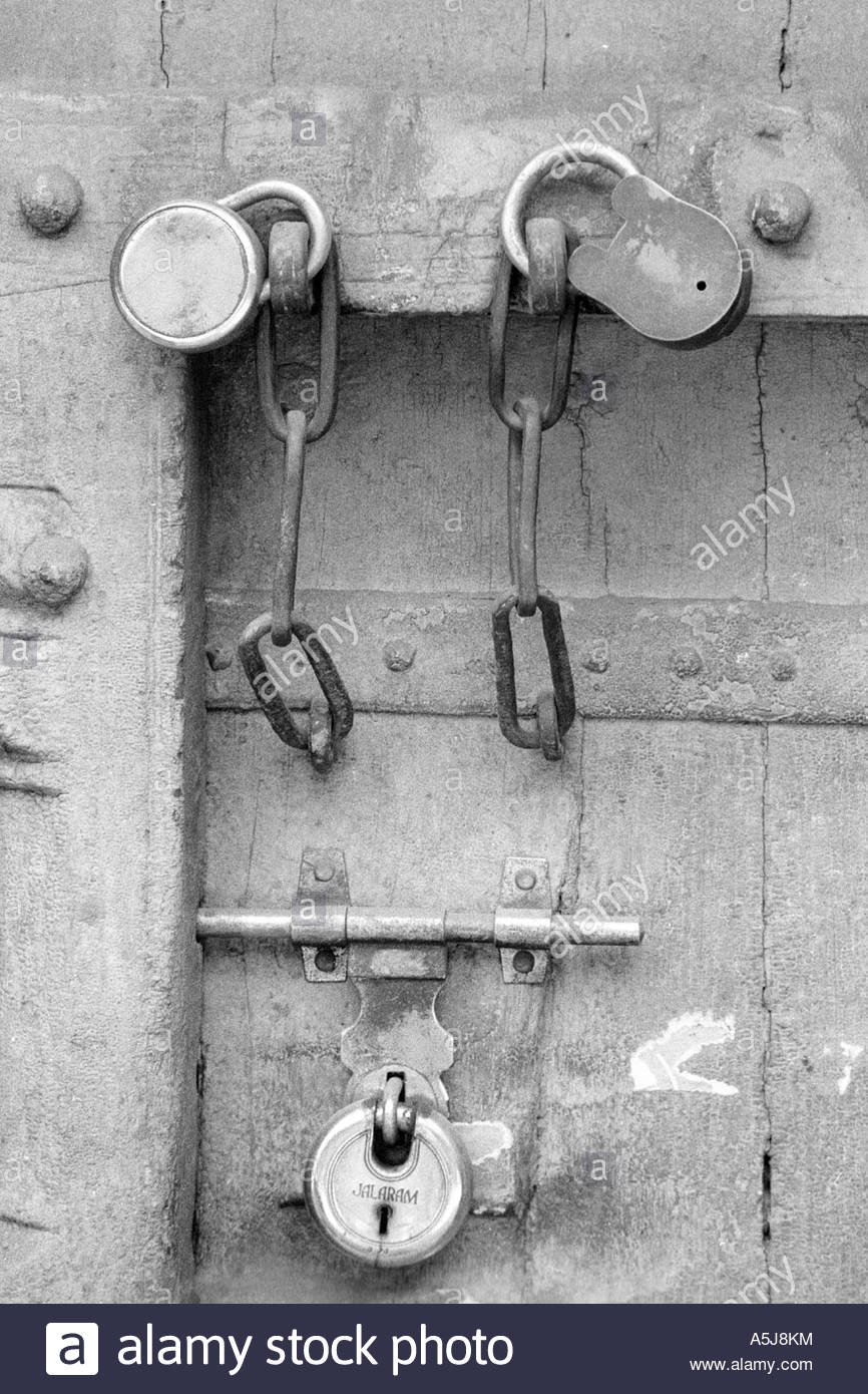 three locks on shop door in old city Ahmedabad Gujarat India - Stock Image