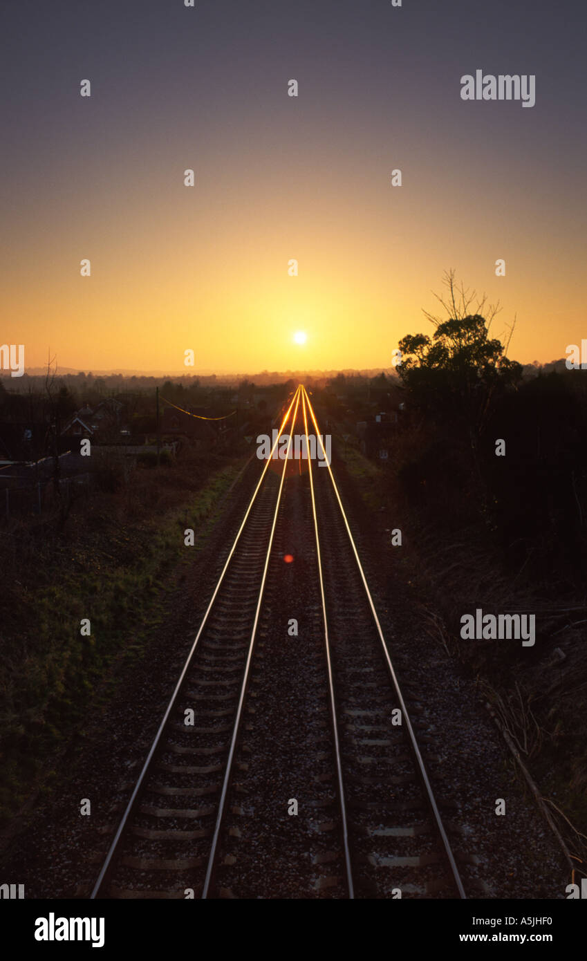 Railway track leading directly towards the setting sun on the distant horizon in Bradford Abbas village Dorset county England UK - Stock Image
