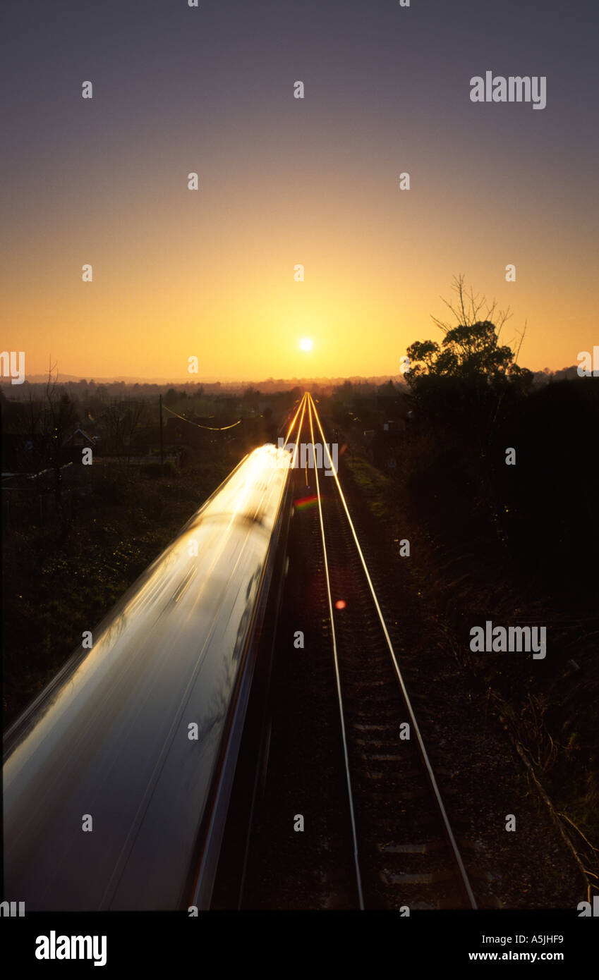 Train driving directly towards the setting sun on the distant horizon in Bradford Abbas village Dorset county England UK - Stock Image