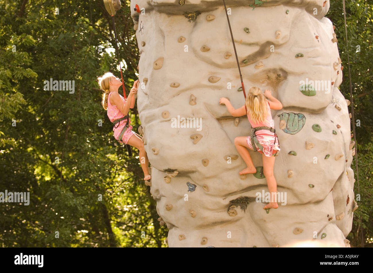 Girl climbing a rock wall at the Illinois State Fair in Springfield Illinois - Stock Image
