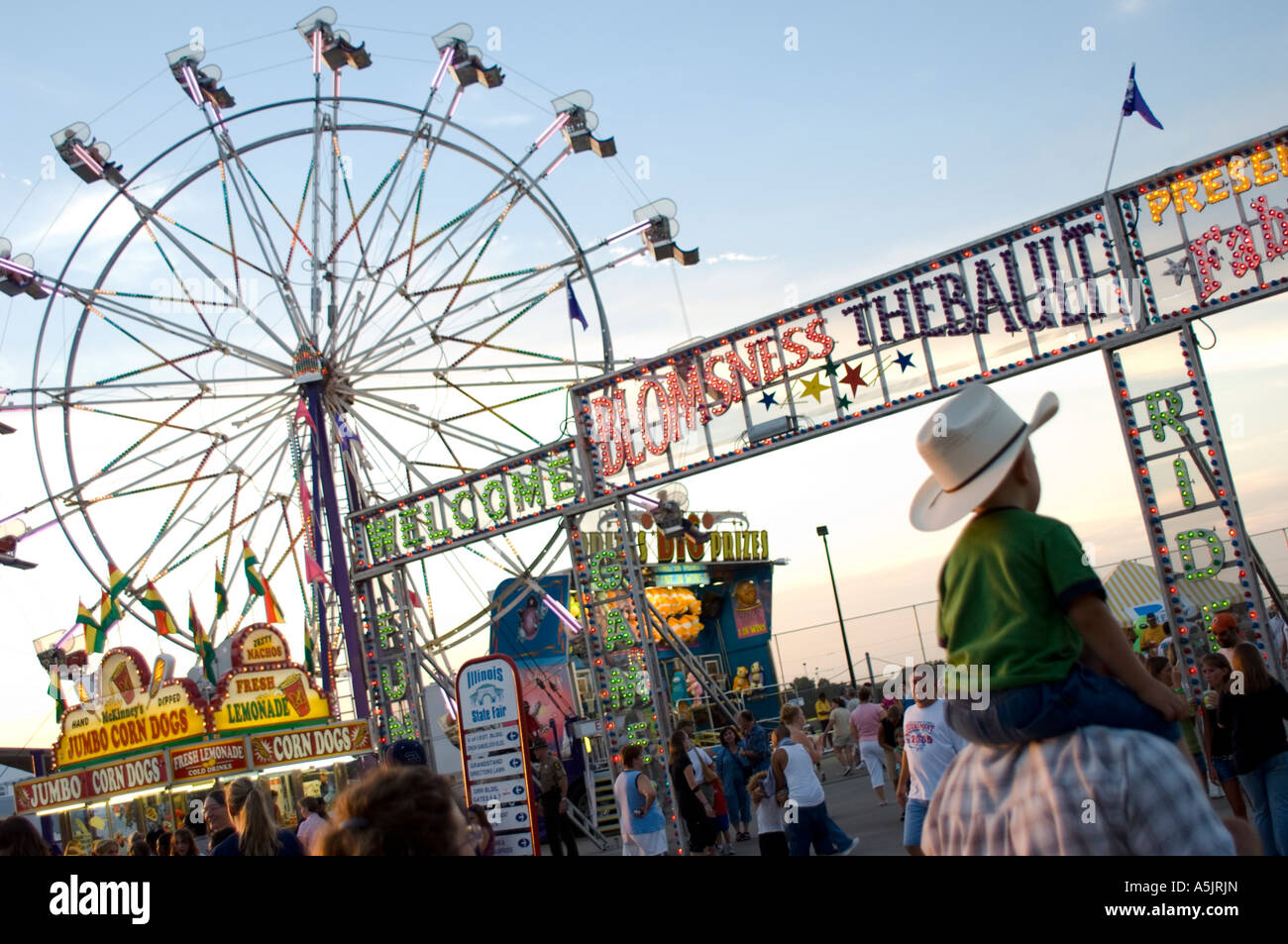 Kid on dads shoulders walking into the Illinois State Fair in Springfield Illinois - Stock Image