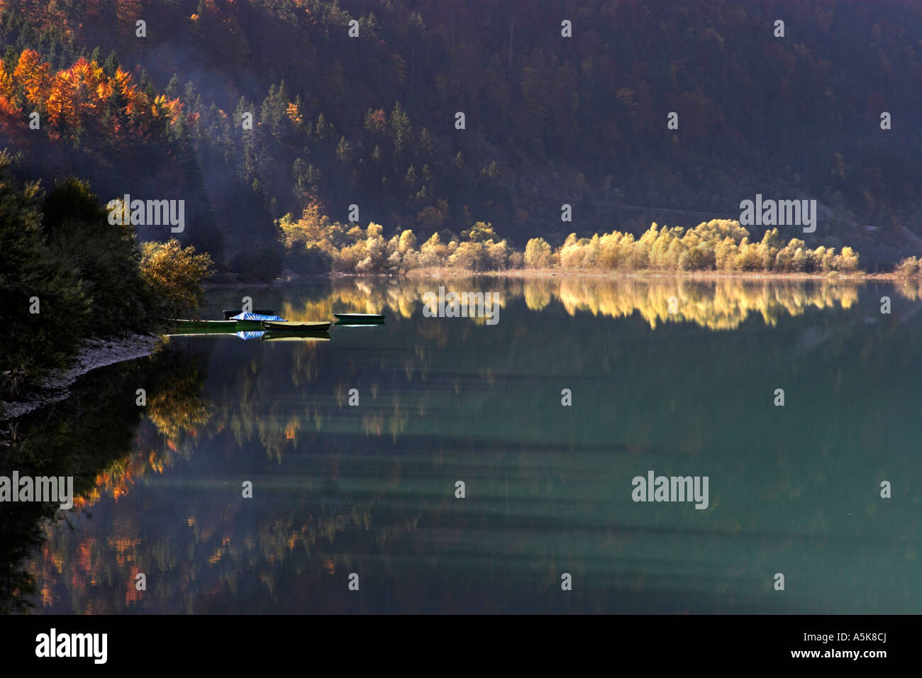 Automnal Sea in the Early morning glow, 3 three rowboats, Bavaria, Germany - Stock Image