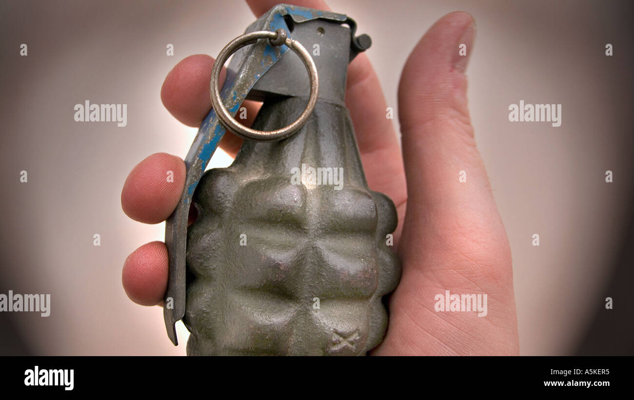 Hand grasping a hand grenade Familiar pineapple form M21 grenade USA - Stock Image