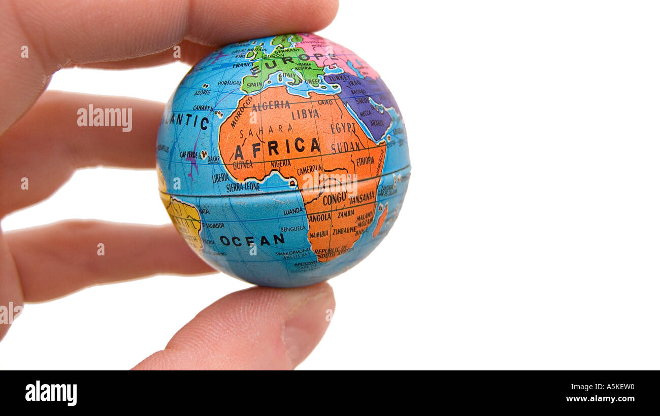 Small globe of Planet Earth held between the fingers of one hand Africa central - Stock Image