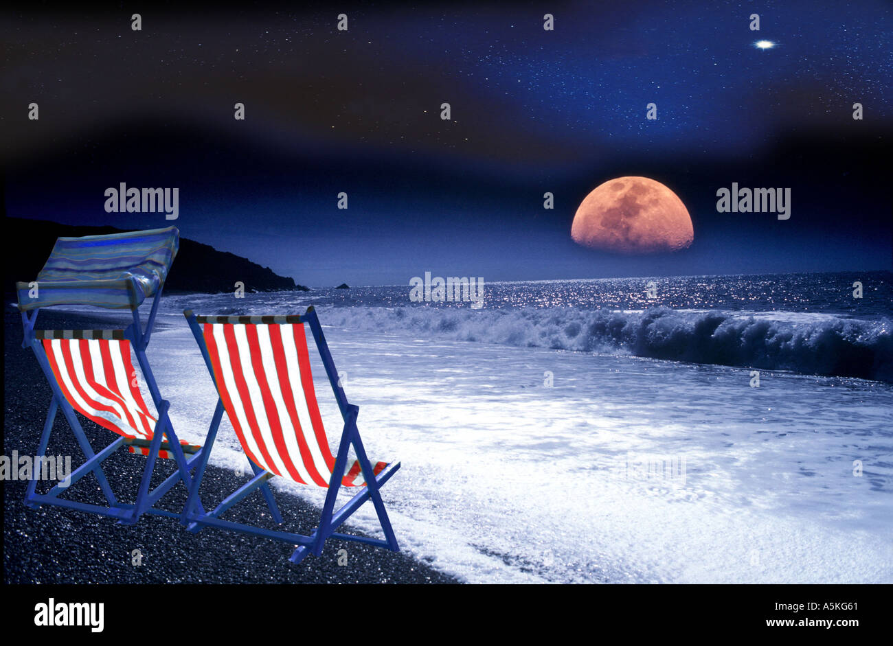 Large moonrise over deserted beach with deckchairs Isle of Wight England - Stock Image