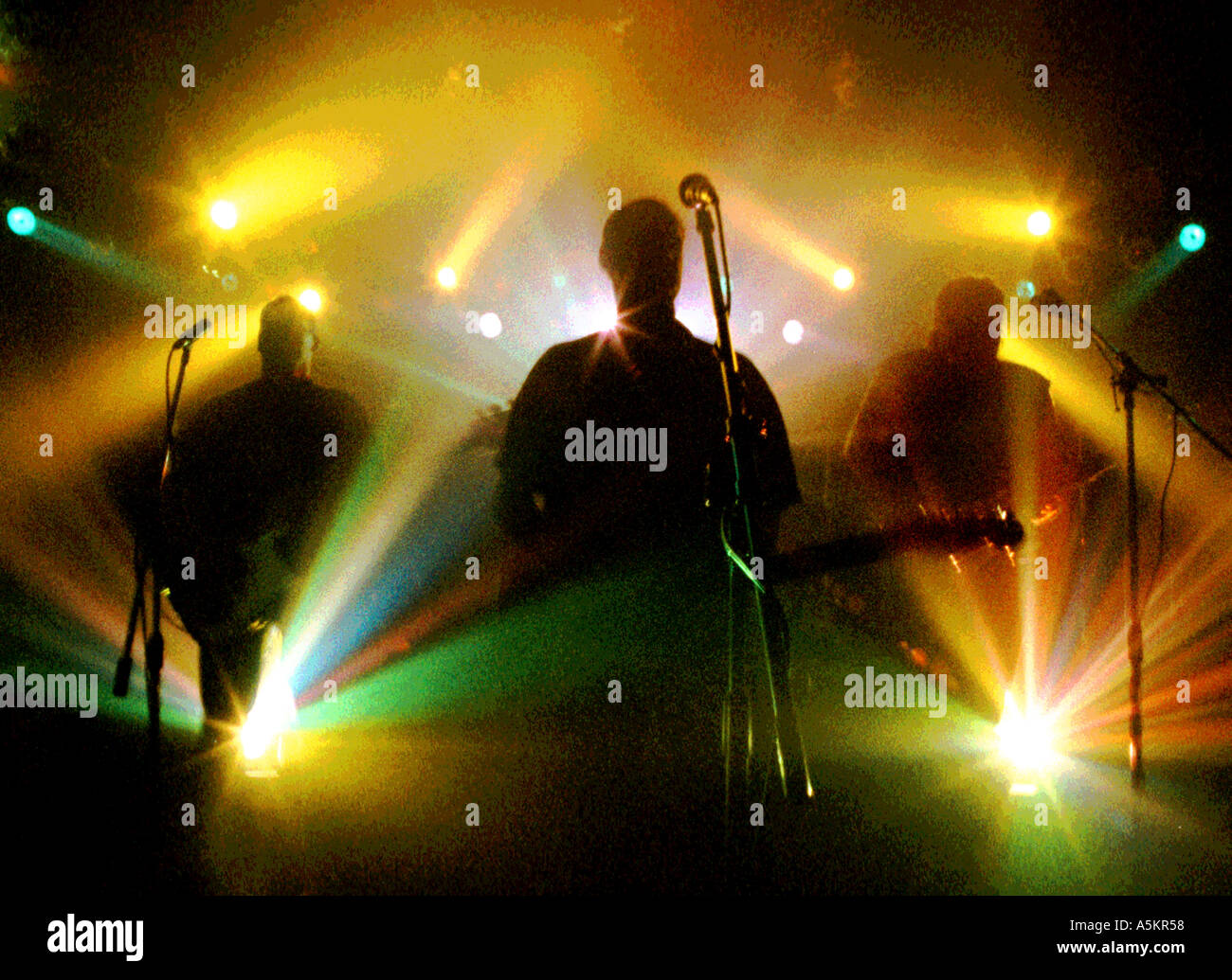 Silhouette of Floydian Slip playing Pink Floyd tribute with psychedelic stage lighting - Stock Image