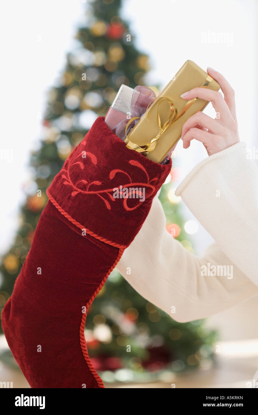 Woman stuffing gifts into Christmas stocking - Stock Image