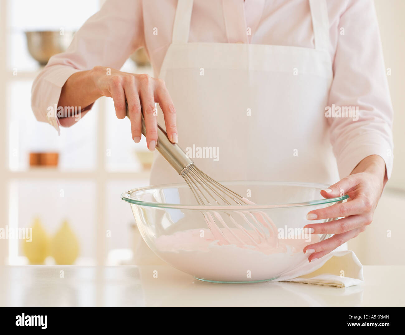Woman wearing apron and mixing batter - Stock Image