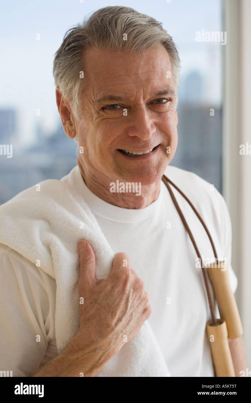 Portrait of senior man holding jump rope over shoulder Stock Photo