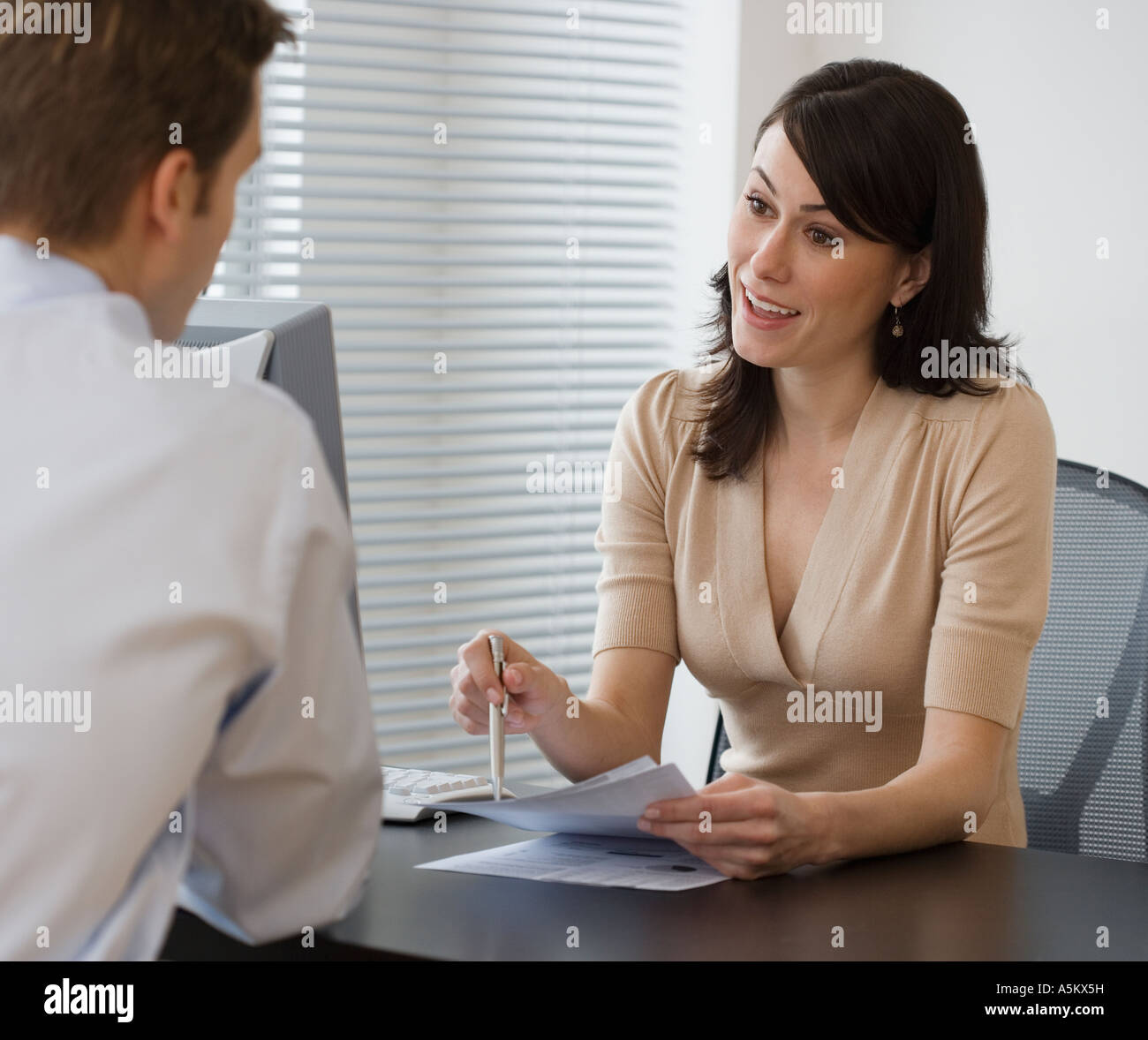 Businesswoman talking to co worker at desk - Stock Image