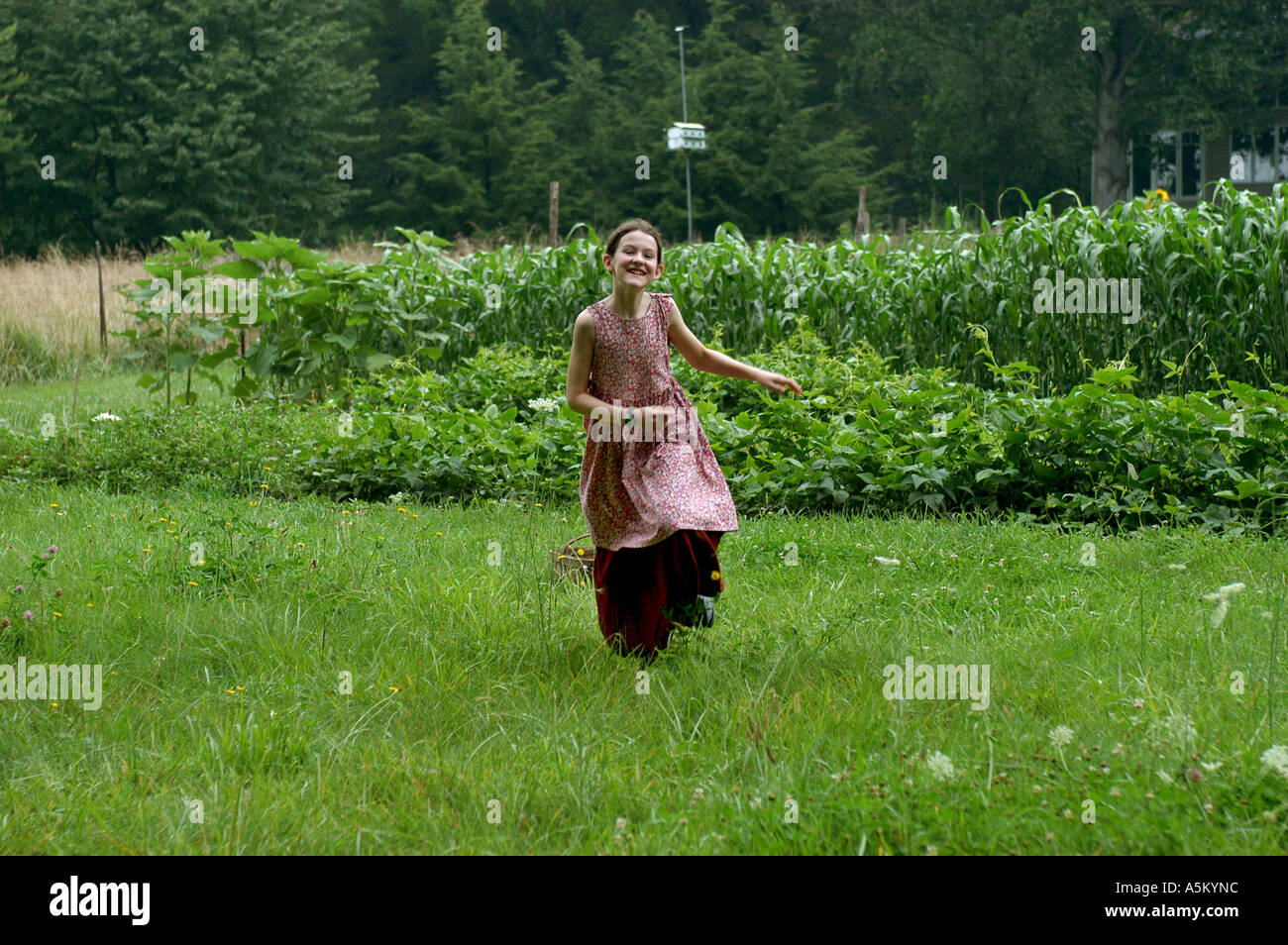 cf0a2513b18 An eleven year old girl wearing a pioneer style dress runs freely through a  lush green