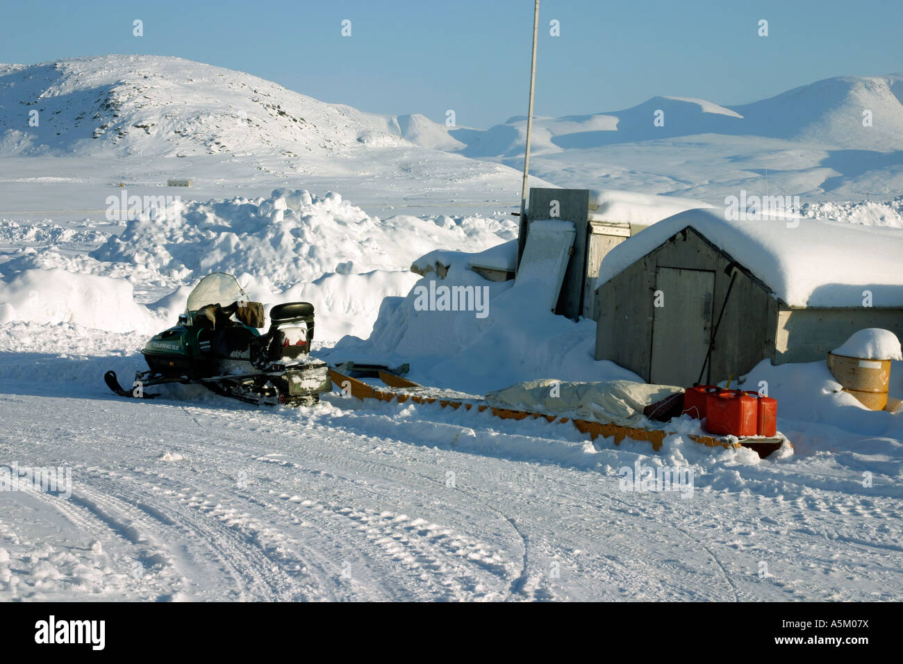 A snowmobile and sledge belonging to an Inuit hunter in Qikitarjuaq, Baffin Island, Canadian Arctic - Stock Image