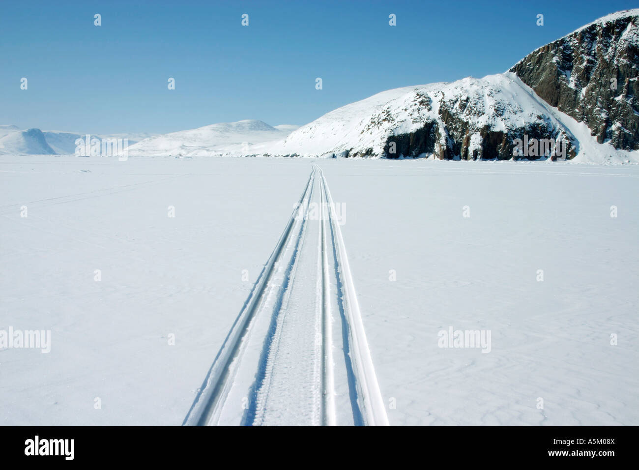 Snowmobile tracks on sea ice with snow covered hills behind, near the Inuit community of Qikitarjuaq on Baffin Island - Stock Image