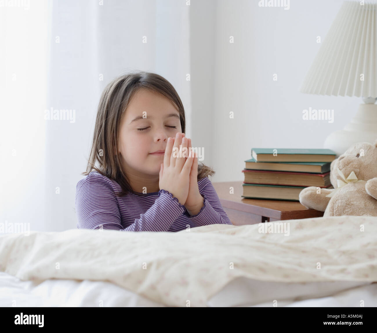 Girl praying next to bed - Stock Image