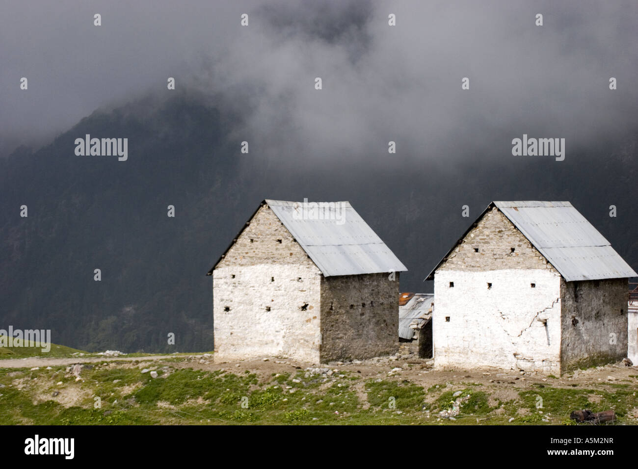 Two stone houses near Keylong in the Himalayan region of Ladakh. - Stock Image
