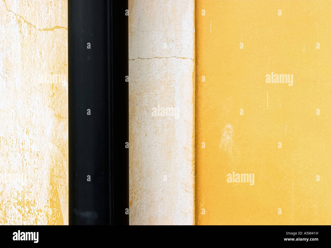 Abstract wall with crossing black drainpipe - Stock Image