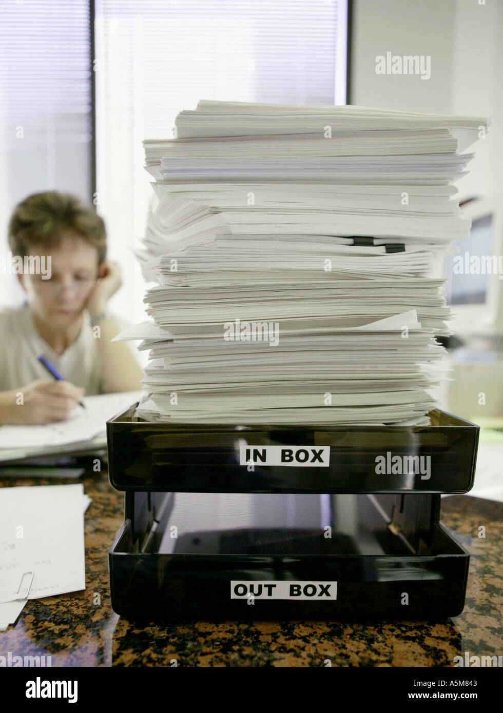 female office worker at desk with vast amouts of paper stacked on inbox - Stock Image