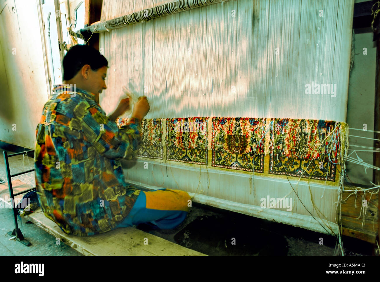 Saqqarah Egypt, Young Boy Working, Weaving CARPET IN Factory, Underage Adolescent at Work on Rug - Stock Image