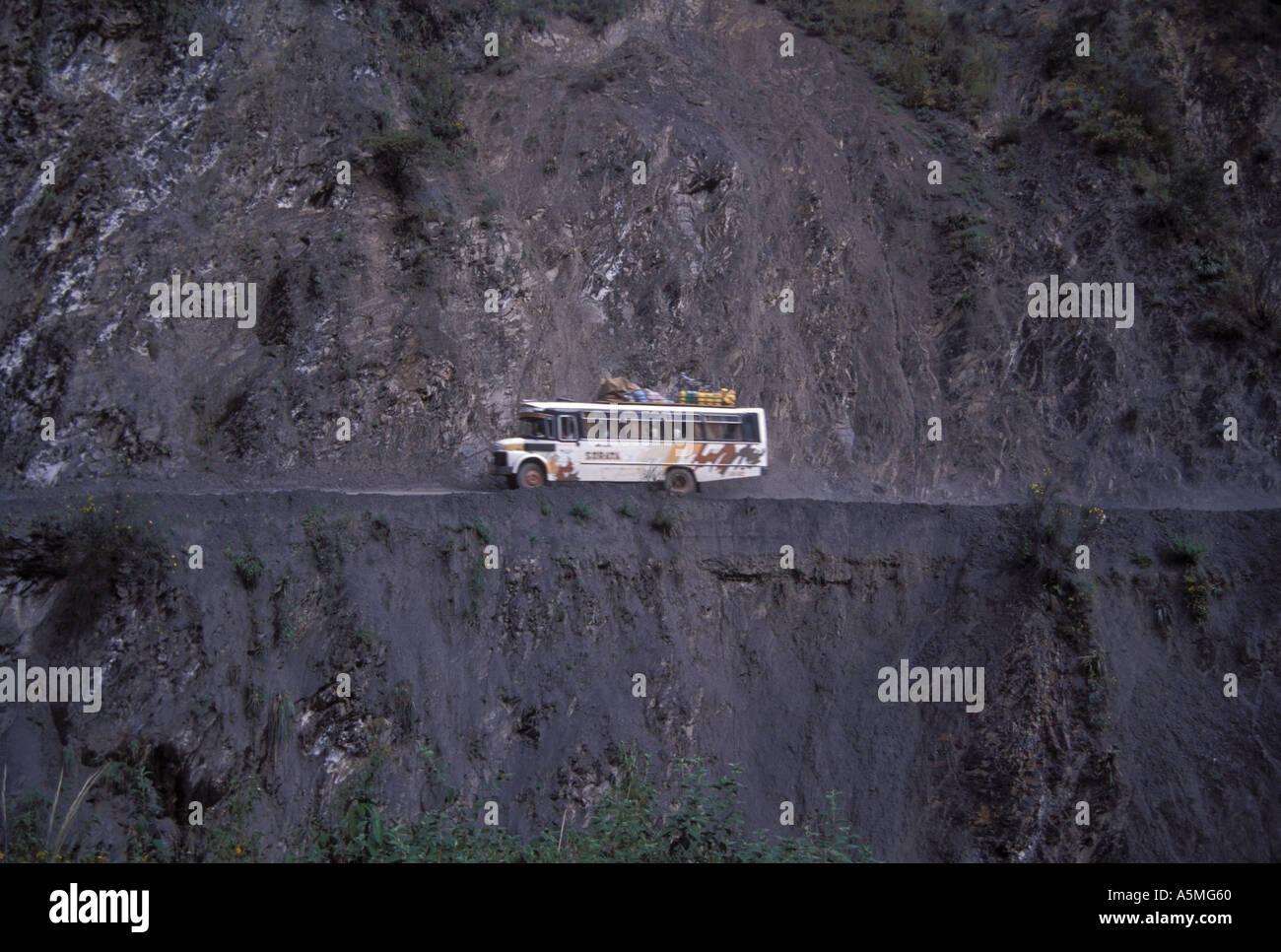 Bus driving along exposed dangerous road along mountain side Sorata Bolivia - Stock Image