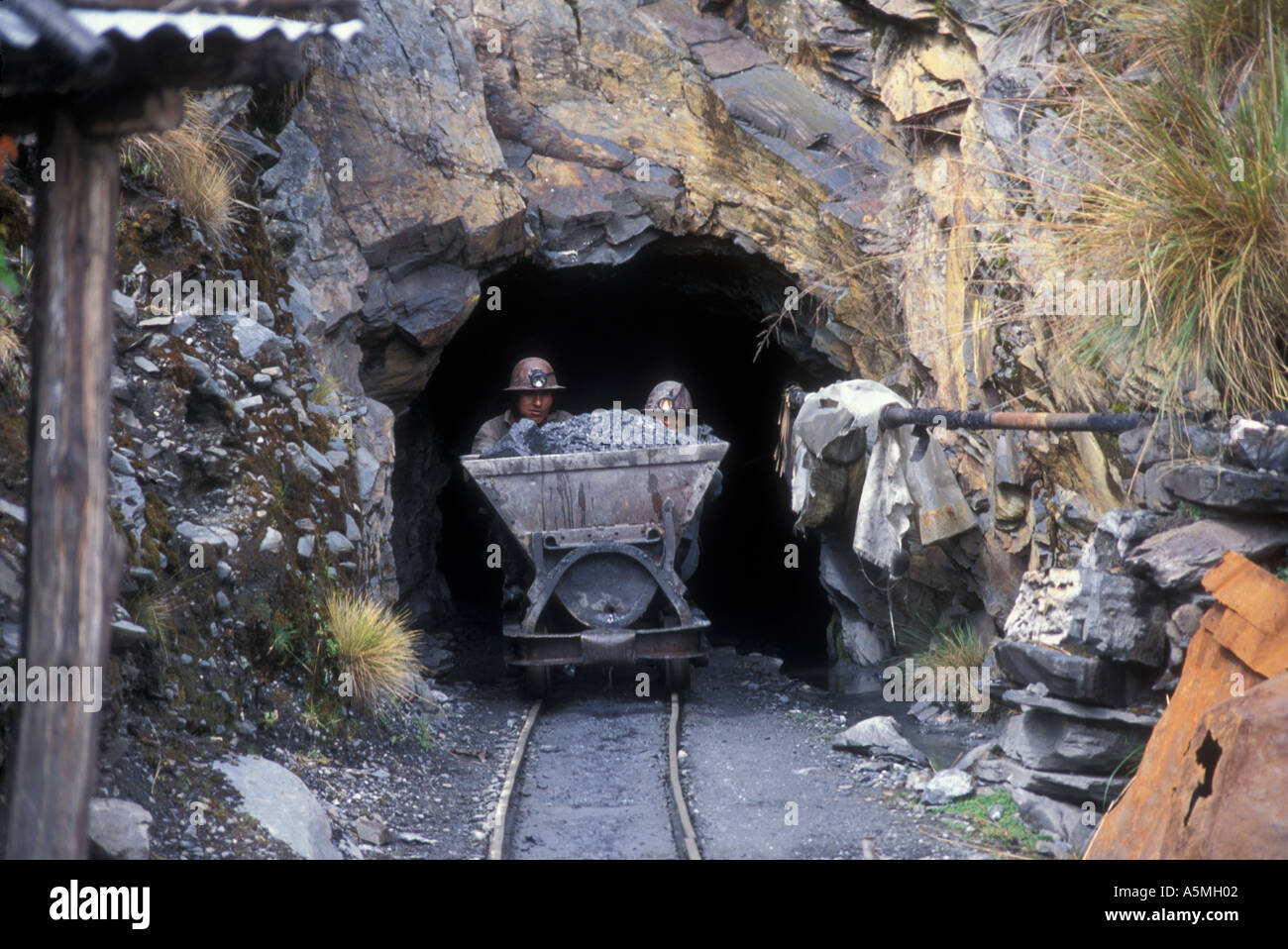 Goldminers push gravel cart out of tunnel appr 4500 Meters altitude Sorata Coop mining Cordillera Real Andes Bolivia - Stock Image