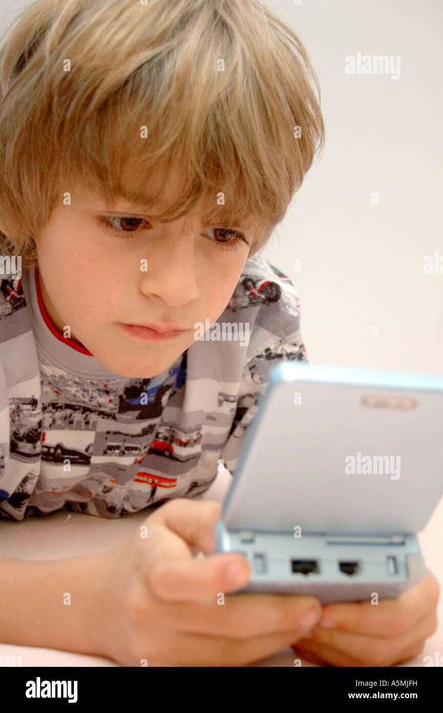 Junge spielt am Gameboy boy playing with Gameboy Kind Menschen Mensch Personen Leute people jung kindlich Kinder Stock Photo