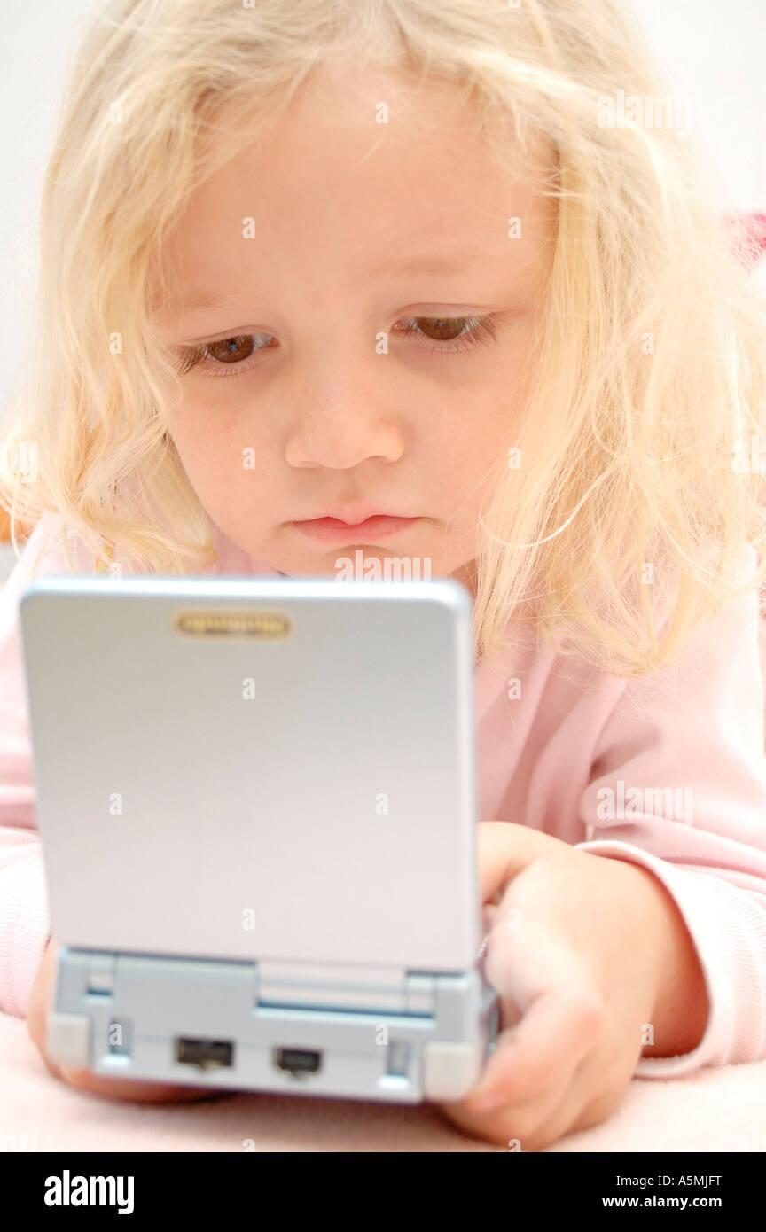 4 jähriges Mädchen spielt mit Gameboy four years old girl playing with Gameboy Kind Menschen Mensch Personen Leute Stock Photo